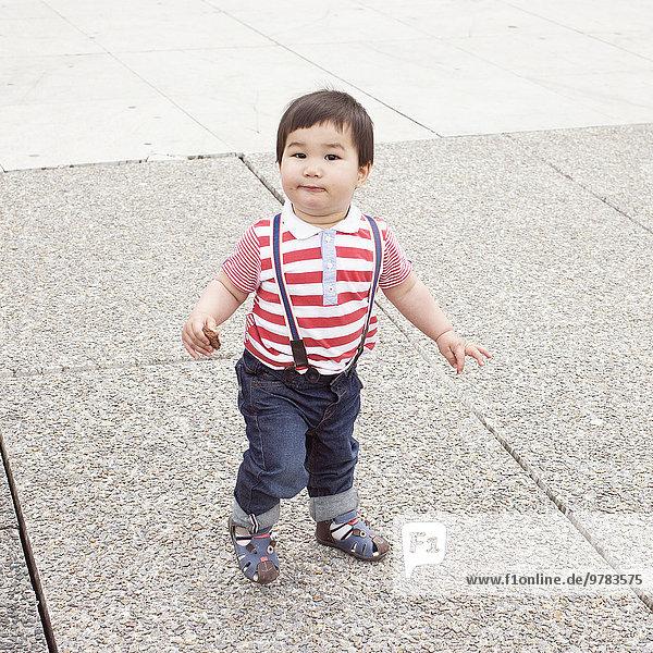 Kleiner Junge auf dem Bürgersteig mit Snack in der Hand