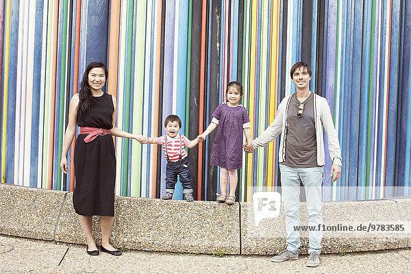 Familie hält Hand in Hand vor bunter Streifenskulptur  La Defense  Paris  Frankreich