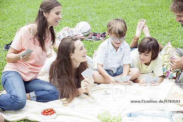 Familie mit Picknick und Kartenspiel
