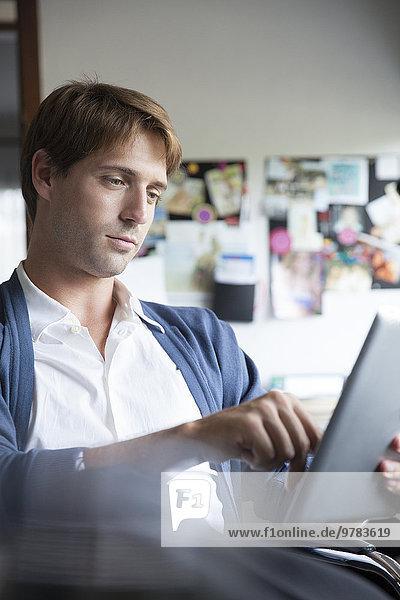 Mann mit digitalem Tablett im Büro