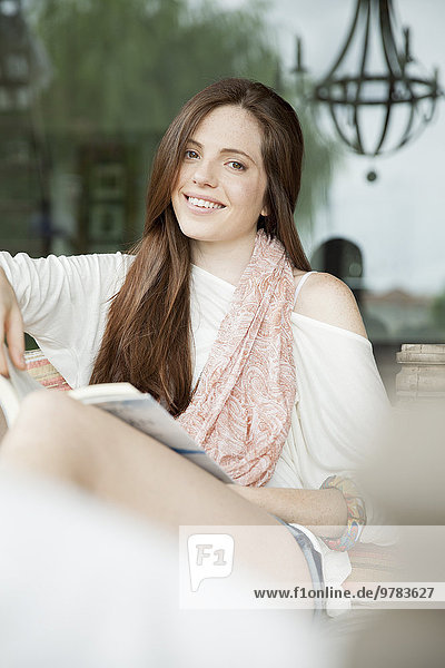 Junge Frau entspannt sich im Freien mit Buch