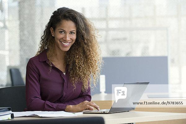 Geschäftsfrau mit Laptop im Büro  lächelnd  Portrait