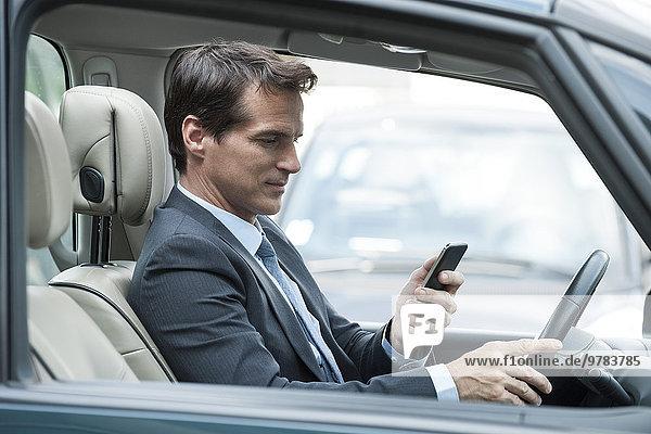 Mann  der während der Fahrt auf sein Handy schaut.