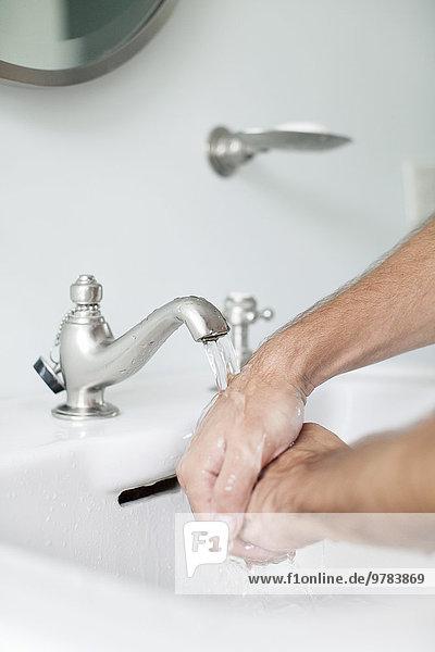 Mann beim Händewaschen im Waschbecken