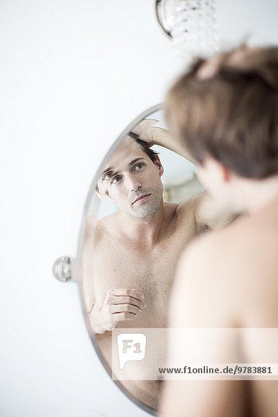 Mann untersucht Haaransatz im Spiegel