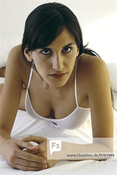 Frau in Unterwäsche auf dem Bett liegend  verführerisch in die Kamera schauend