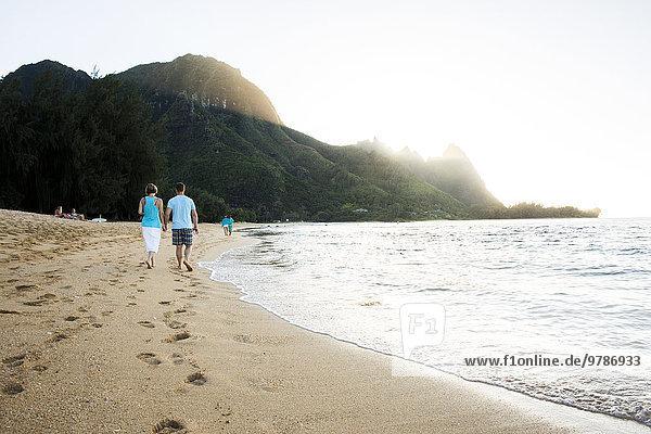 Couple walking together near ocean on beach