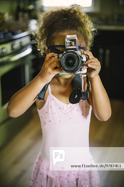Mixed race girl photographing with camera