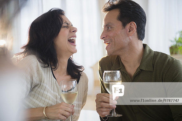 Couple laughing and drinking white wine