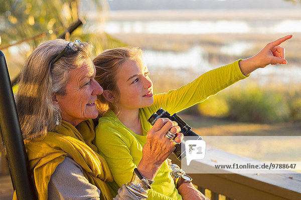 Caucasian grandmother and granddaughter using binoculars on porch