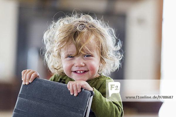 Caucasian baby boy holding digital tablet