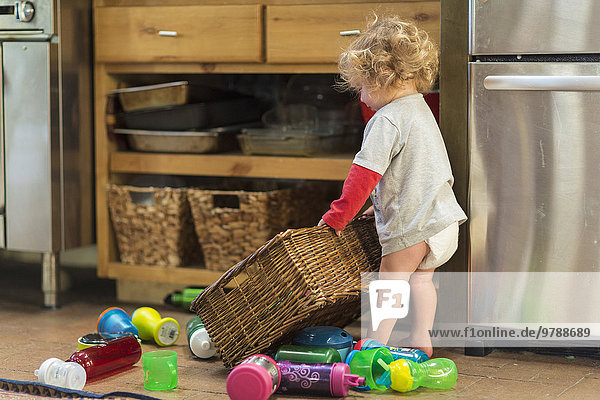 Caucasian baby boy playing with toys and basket
