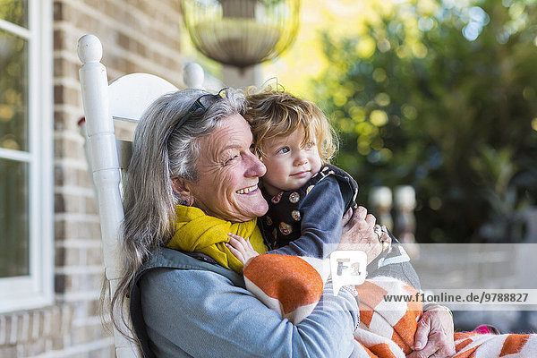 Caucasian grandmother and grandson sitting on porch