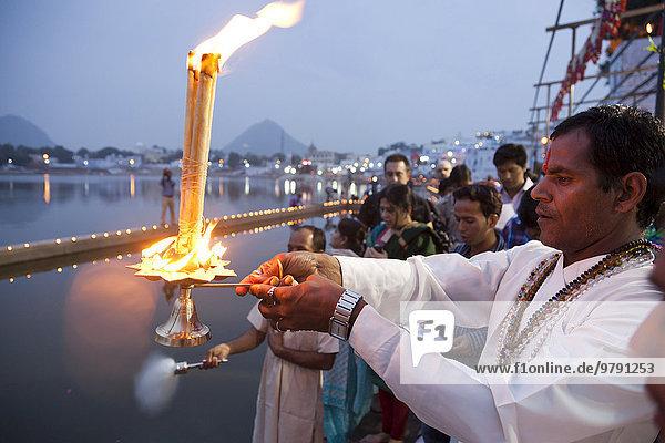 Brahmin conducting a religious ceremony  Aarti and Deepdan ceremony holding an oil lamp  sacred Pushkar Lake during the Pushkar Mela  Rajasthan  India  Asia