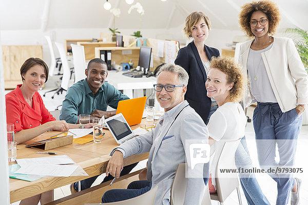 Gruppenporträt von lächelnden Büroangestellten am Tisch