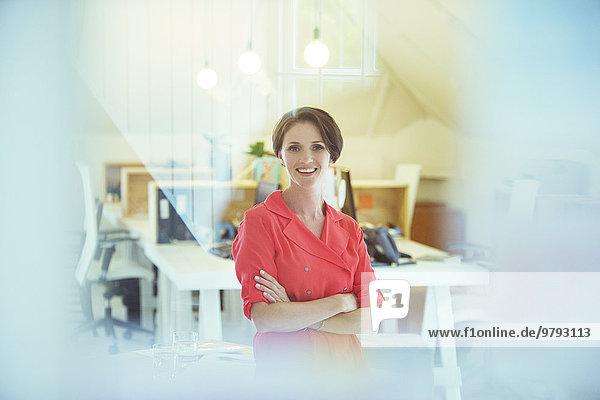 Porträt eines lächelnden Büroarbeiters mit gekreuzten Händen