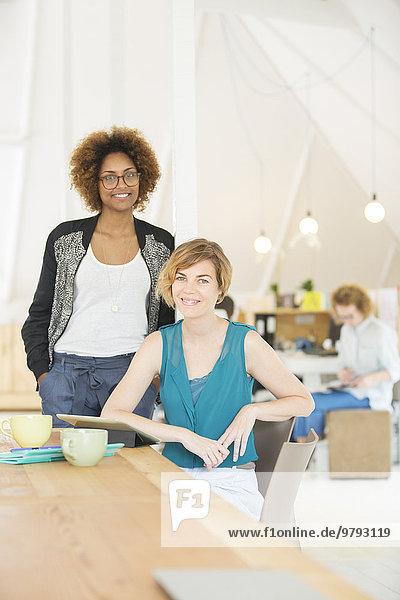 Porträt von zwei lächelnden Büroangestellten am Schreibtisch