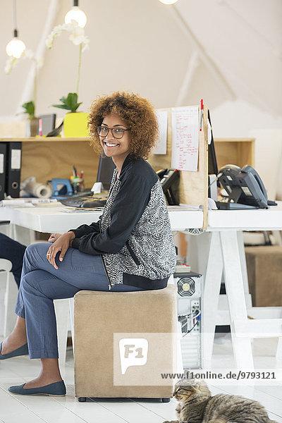 Junge lächelnde Frau am Schreibtisch sitzend