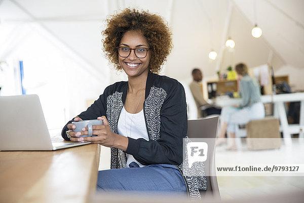 Büroangestellte mit Kaffee am Laptop