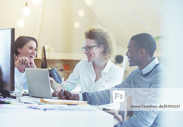 Büroangestellte im Gespräch über Laptop am Schreibtisch