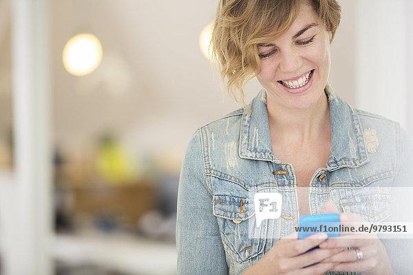 Lächelnder Büroangestellter mit Smartphone