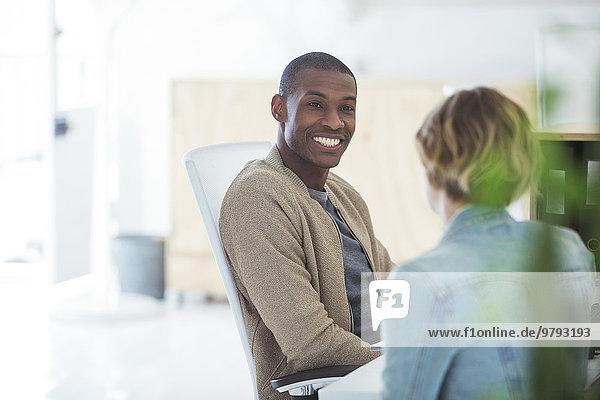 Mann und Frau sitzen im Büro  lächelnd und redend.