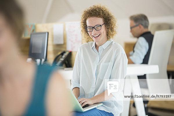 Porträt einer Frau mit Laptop und Lachen  Mann arbeitet im Hintergrund