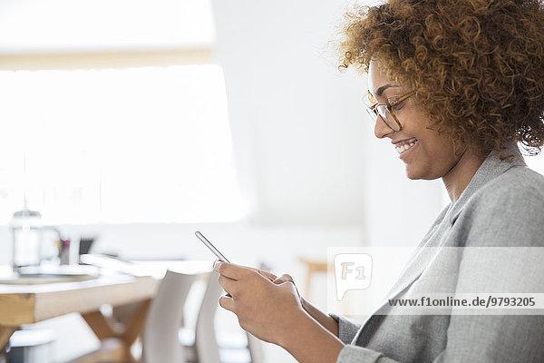 Porträt einer Frau mit Smartphone und Lächeln