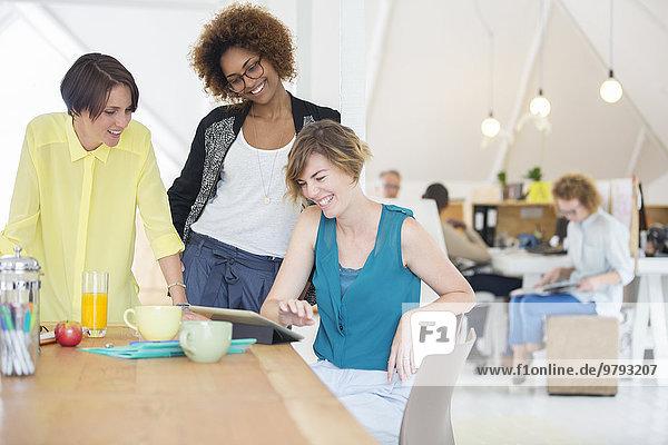 Frauen  die auf das digitale Tablett schauen und im Büro lächeln