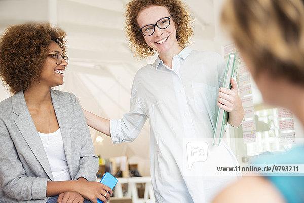 Frauen lächeln und reden im Büro  halten Smartphone und Laptop in der Hand
