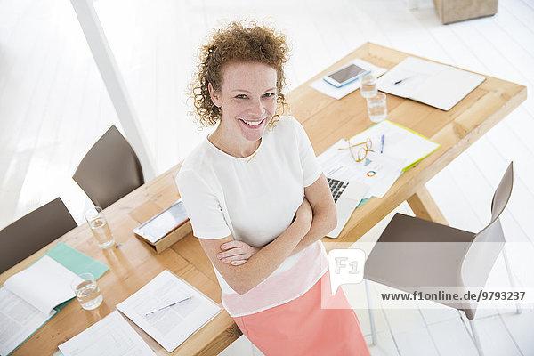 Porträt einer Frau mit verschränkten Armen  lächelnd im Büro