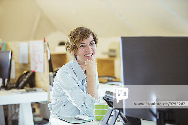 Porträt einer lächelnden Frau im Büro  am Schreibtisch sitzend mit Computer