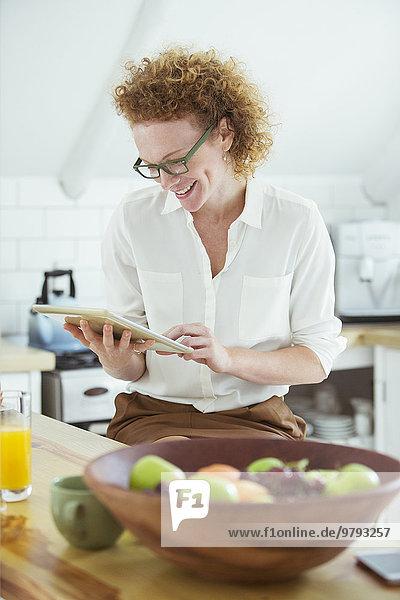 Porträt einer Frau  die in der Küche sitzt und auf das digitale Tablett schaut  lächelnd