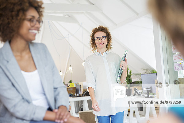 Frau beim Gehen und Tragen des Laptops  mit Kollegin aus dem Büro