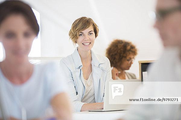 Porträt einer Frau am Schreibtisch sitzend  mit Laptop und lächelnd im Büro  Kollegen im Hintergrund
