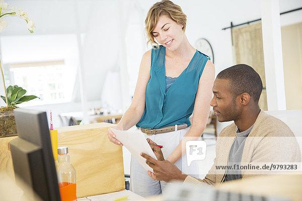 Frau und Mann schauen sich Dokumente an  reden und lächeln im Büro.
