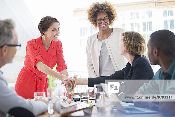 Büroangestellte beim Händeschütteln am Schreibtisch
