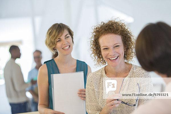 Büroangestellte beim Plaudern und Lachen während der Besprechung