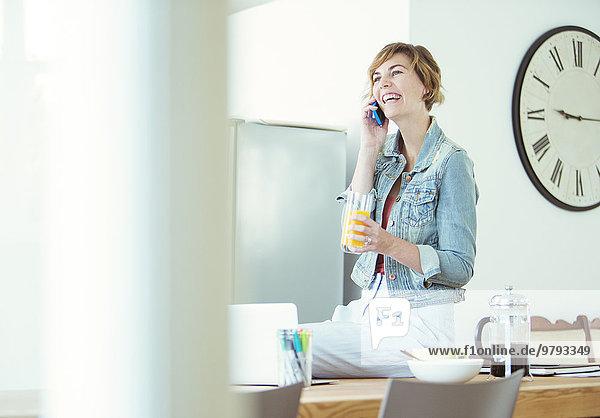 Junger Büroangestellter am Schreibtisch beim Telefonieren