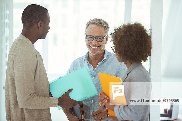 Drei Büroangestellte sprechen im Büro
