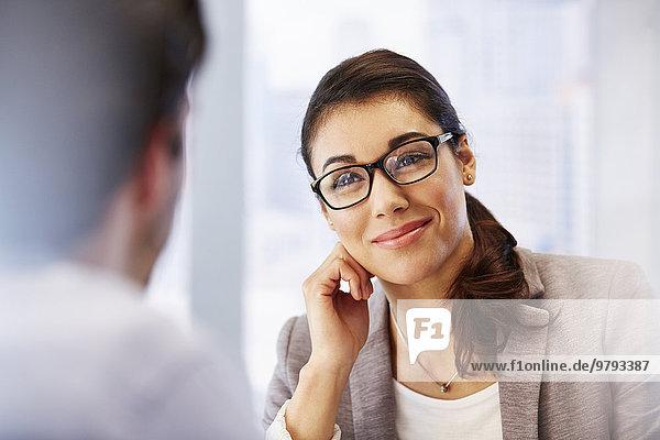 Lächelnde Frau mit Brille im Büro mit Klientin