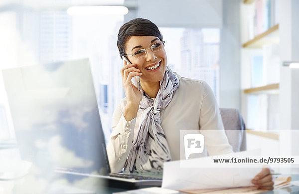 Büroangestellte  die am Schreibtisch sitzt und mit dem Smartphone arbeitet.