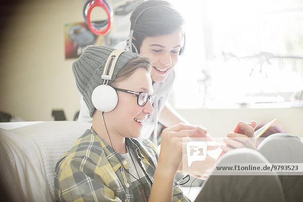 Zwei Teenager  die Musik über Kopfhörer hören.
