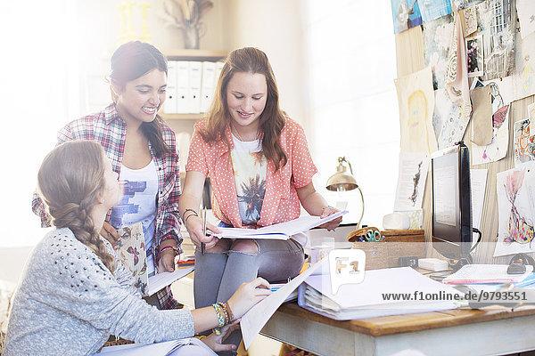 Drei Teenager-Mädchen machen zusammen Hausaufgaben im Zimmer.