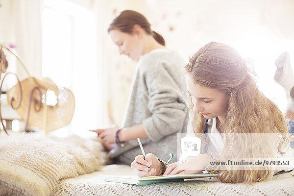Zwei Teenager-Mädchen auf dem Bett schreiben in Notizblöcken