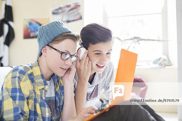 Zwei Teenager-Jungs teilen sich Laptop und Kopfhörer im Zimmer