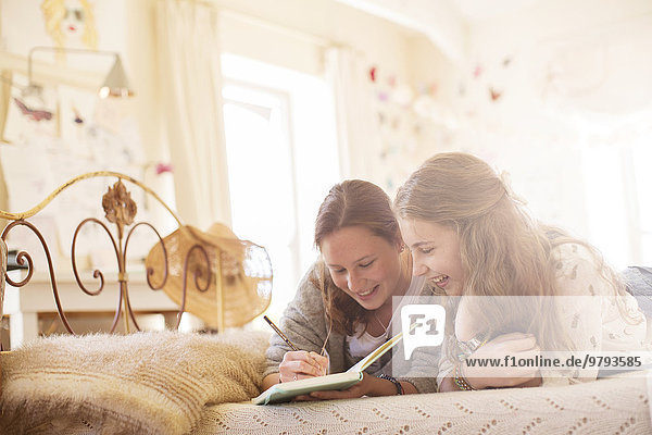 Zwei Teenager-Mädchen liegen auf dem Bett und schreiben in einem Notizbuch.