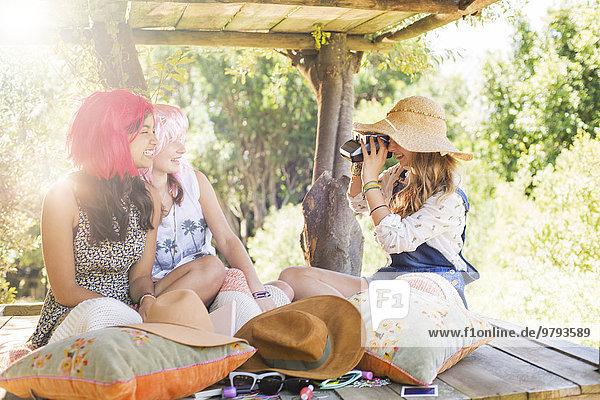Drei Teenagermädchen fotografieren im Baumhaus im Sonnenlicht