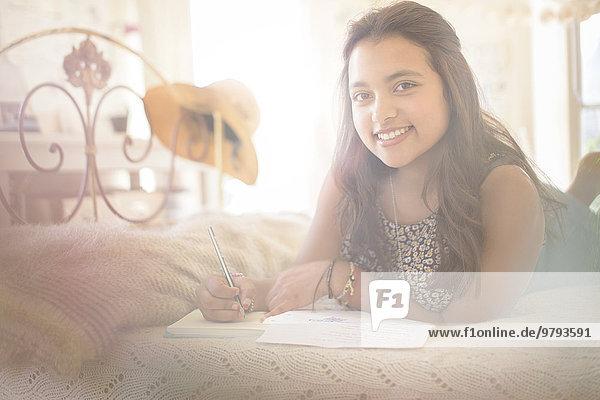 Porträt eines lächelnden Teenagermädchens im Schlafzimmer auf dem Bett liegend