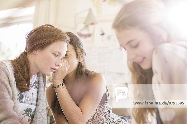 Drei Teenager-Mädchen klatschen im Zimmer.